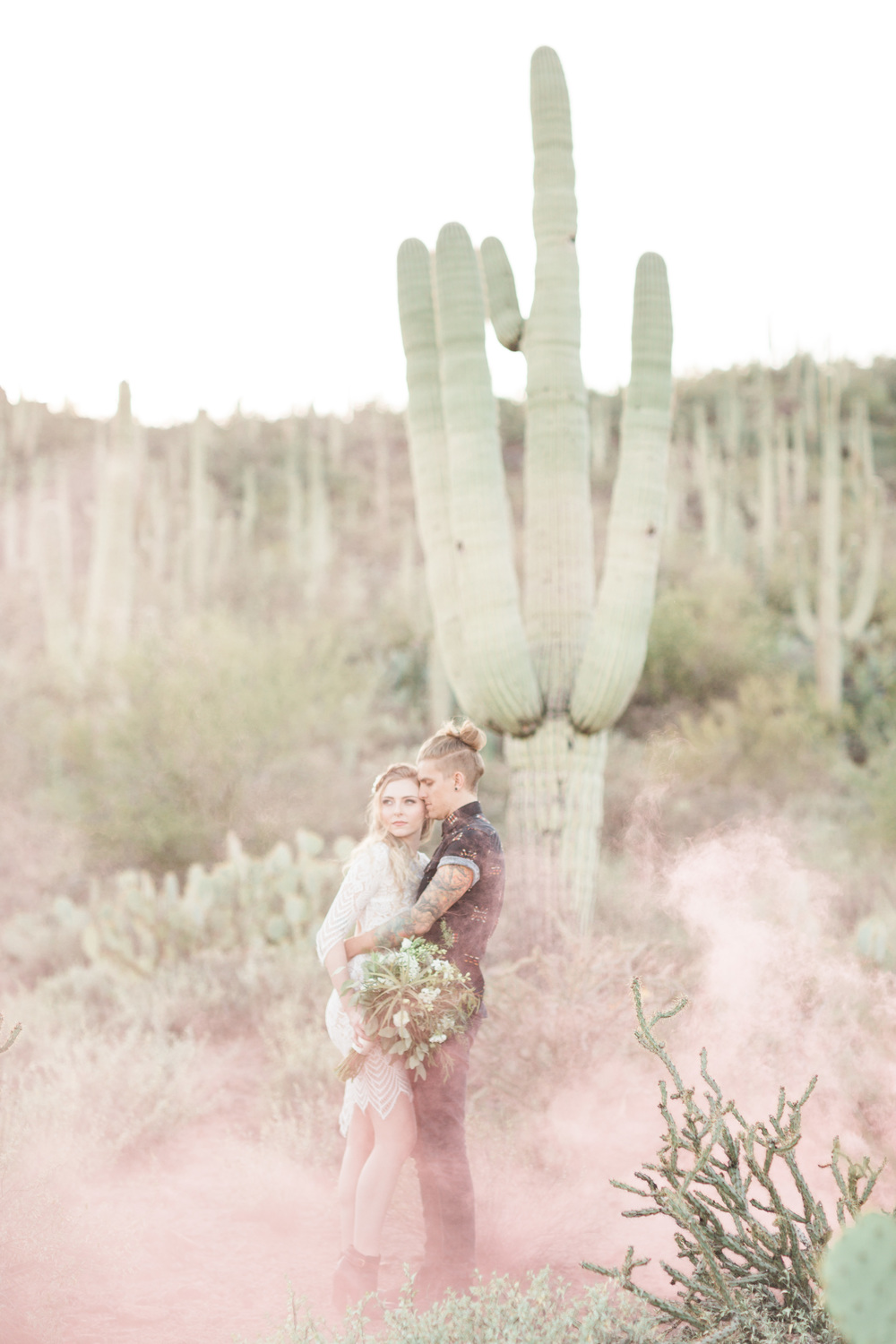 Bride and groom hugging in the desert with cactus in the background and pink smoke surrounding them