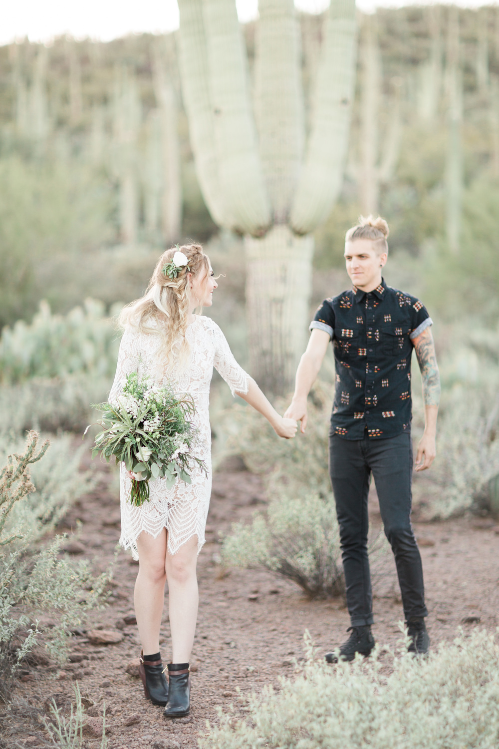 Bride and groom holding hands with huge saguaro in the background