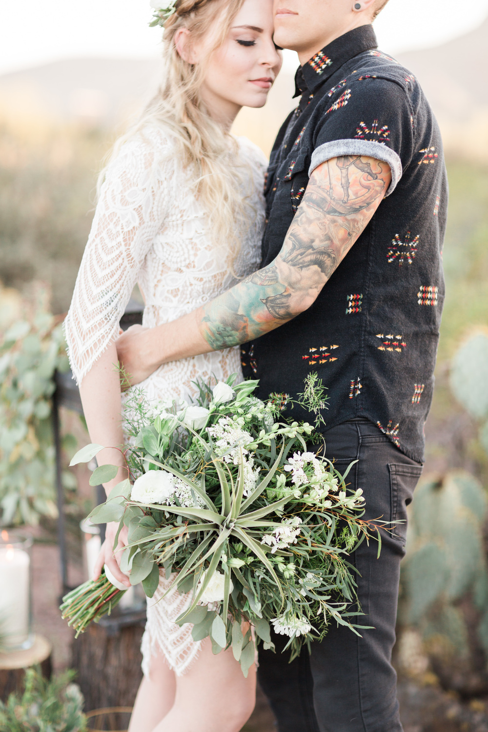 hipster groom hugging his bride who is holding a gorgeous green and white bouquet