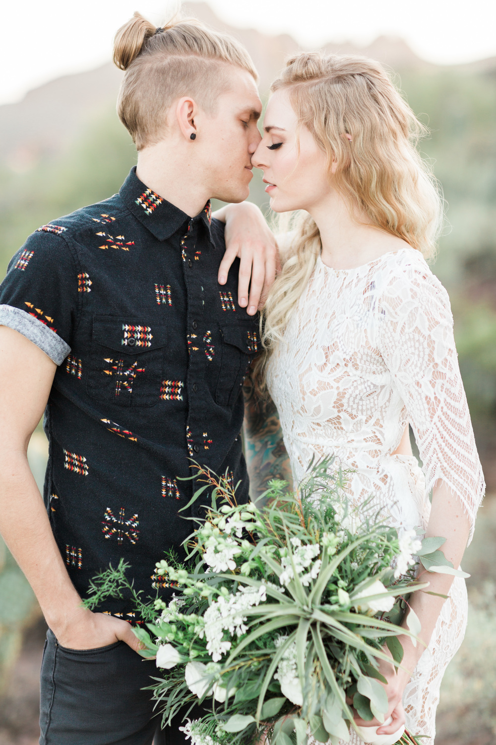 Trendy boho bride holding organic bouquet, kissing her husband with a man bun.