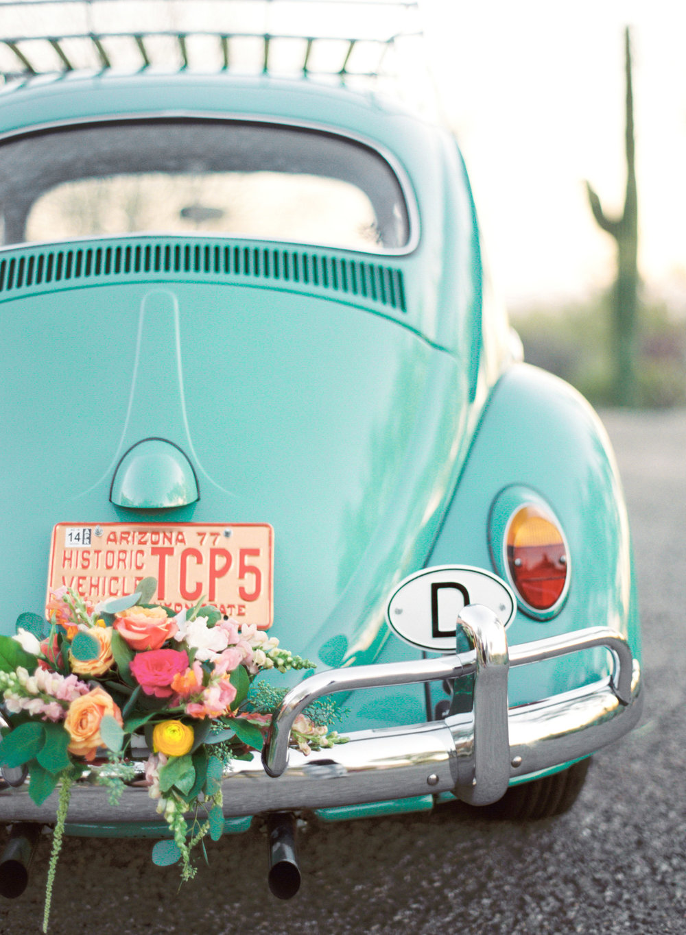 Adorable teal volkswagen beetle wedding car decorated with florals
