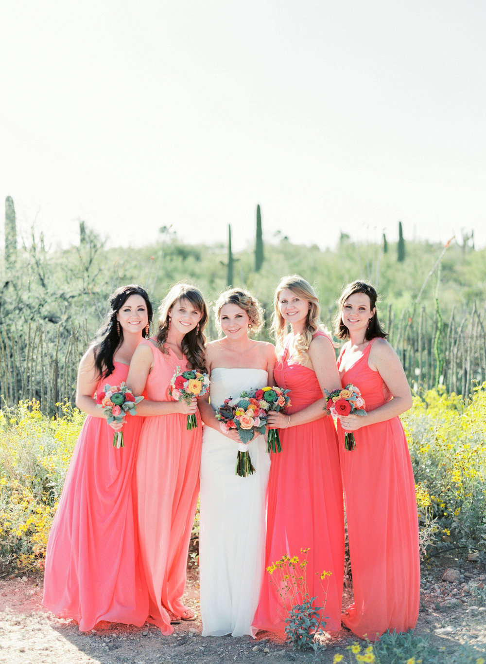 Bride with Bridesmaids in bright pink and salmon dresses