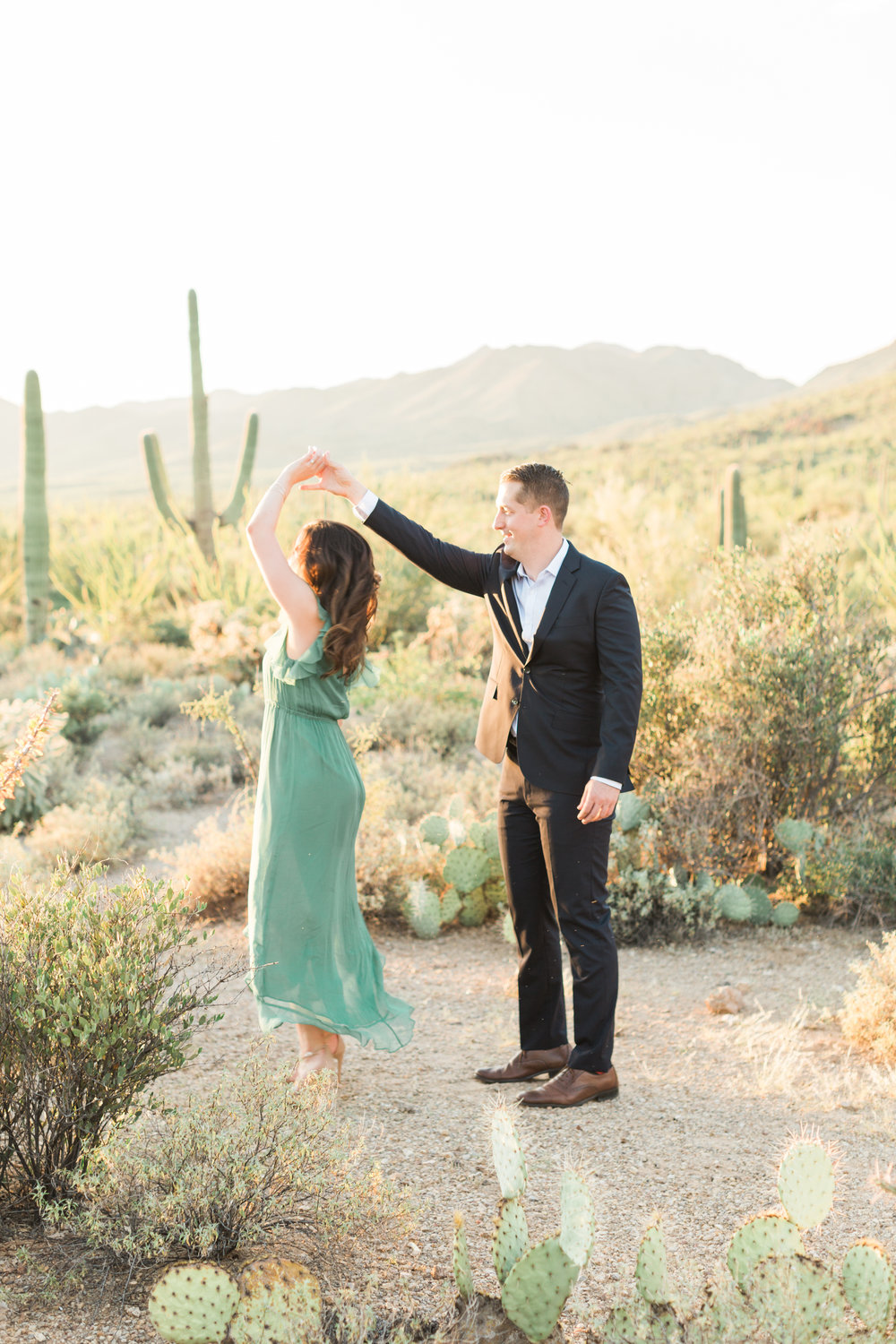Cute couple dancing in the desert at their Tucson engagement session. Gorgeous desert light and cactus glowing in the background.