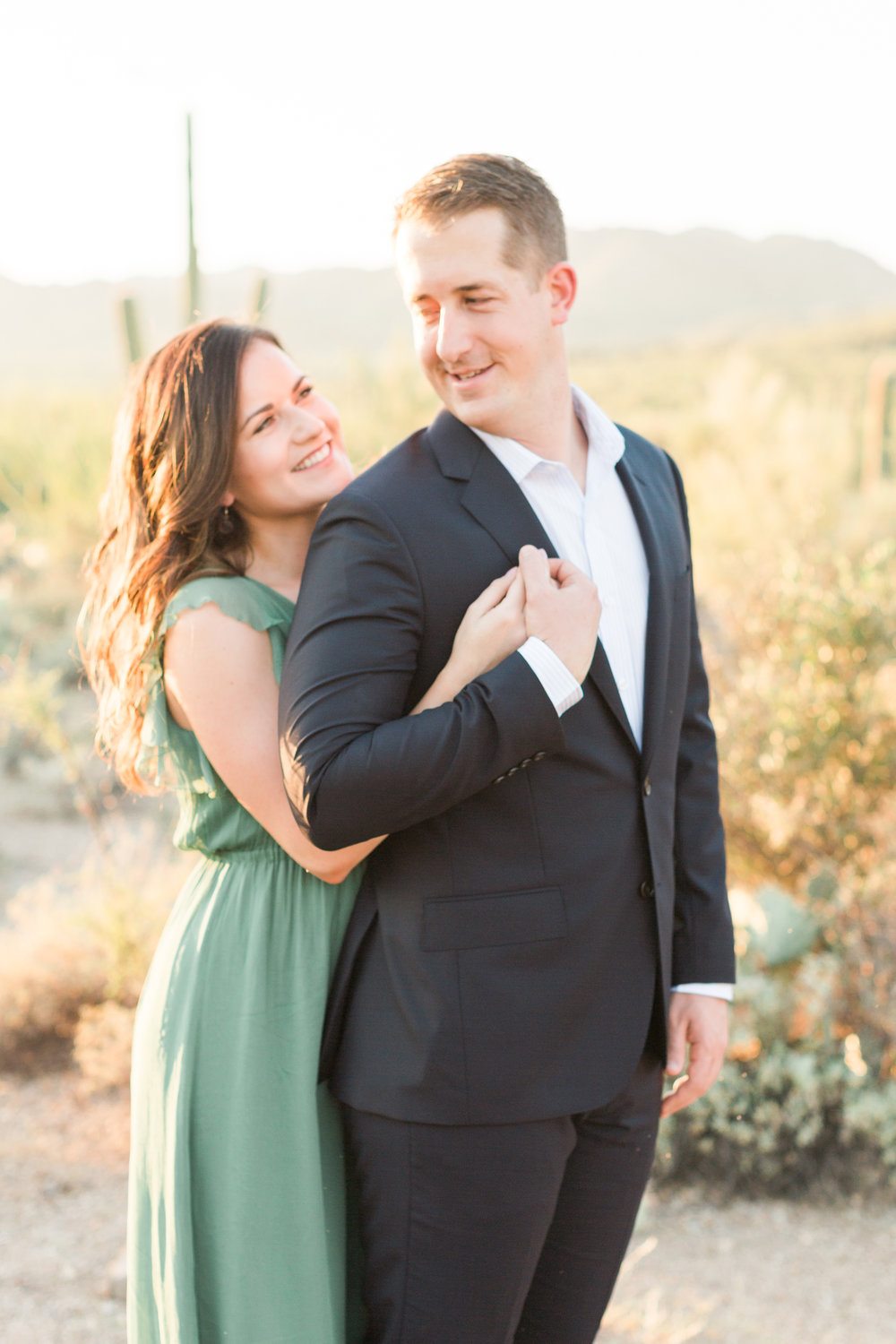 Gorgeous couple hugging at their engagement session in Tucson, AZ with the golden hour desert in the background.