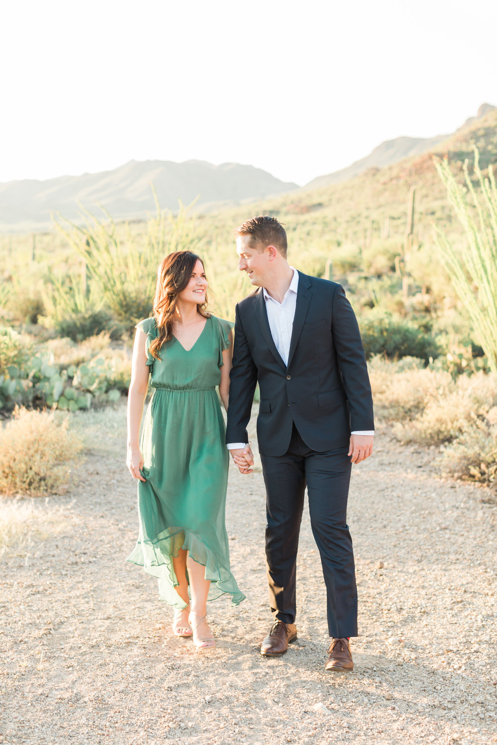 Cute couple walking in the desert. Love all that glowing cactus and gorgeous Tucson mountains in the background!