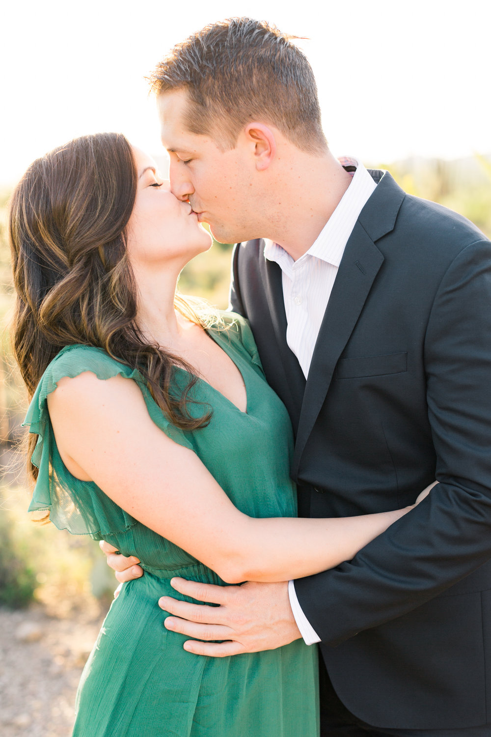 Couple kissing at their engagement session with the golden hour desert in the background. So cute!