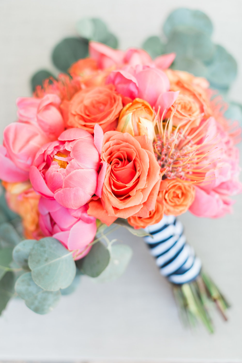 Beautiful bridal bouquet with pink peonies, protea pincushion, salmon and orange roses tied with a striped navy and white ribbon