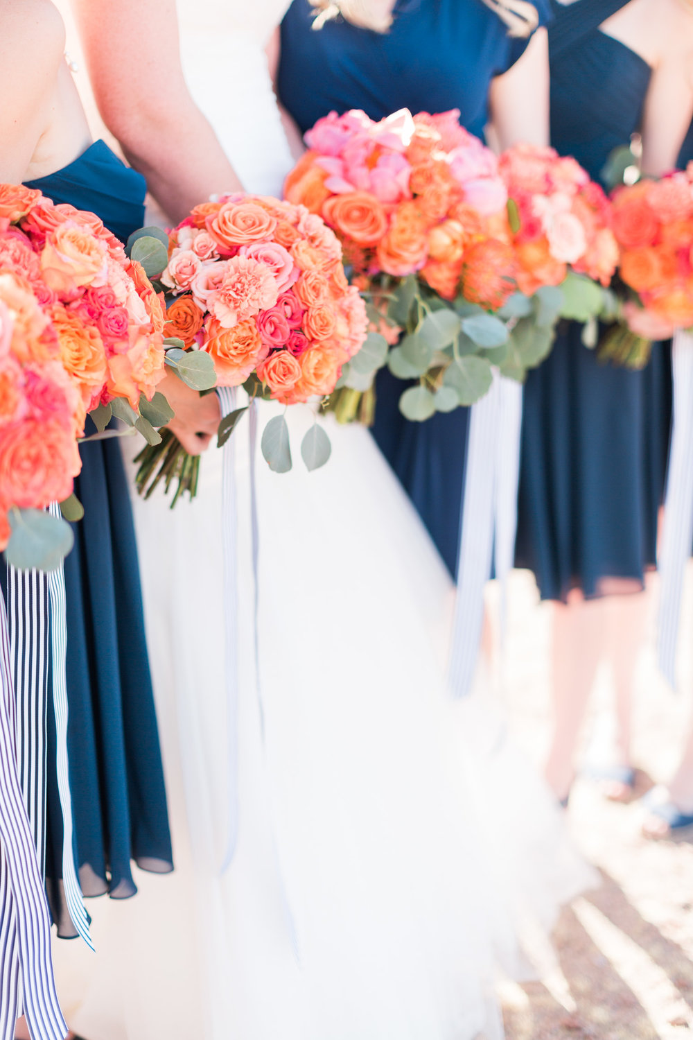 Stunning bouquets with pink peonies, orange and salmon roses with silver dollar eucalyptus.