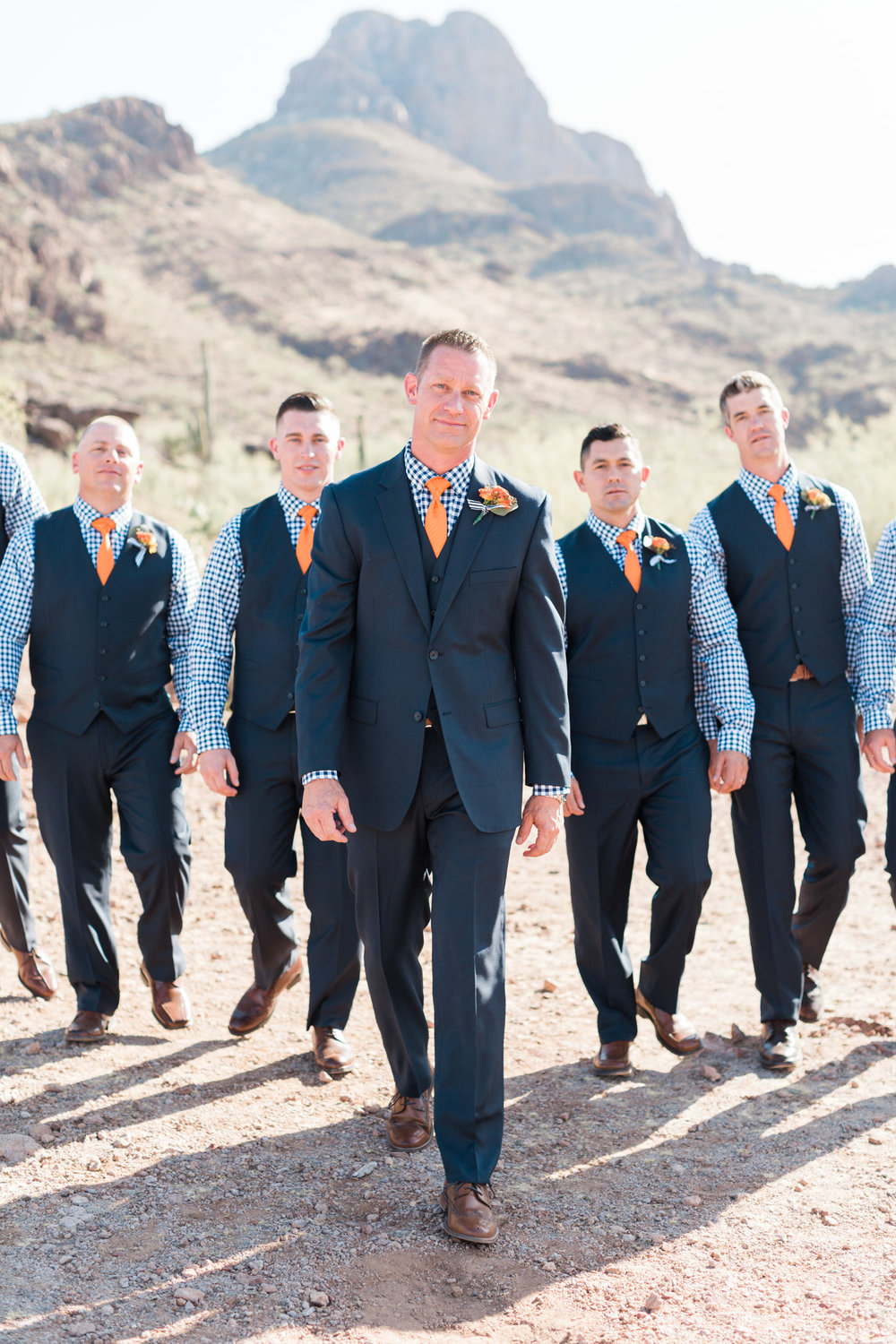 Handsome Groom and groomsmen in navy at Stardance Tucson, walking towards the camera.