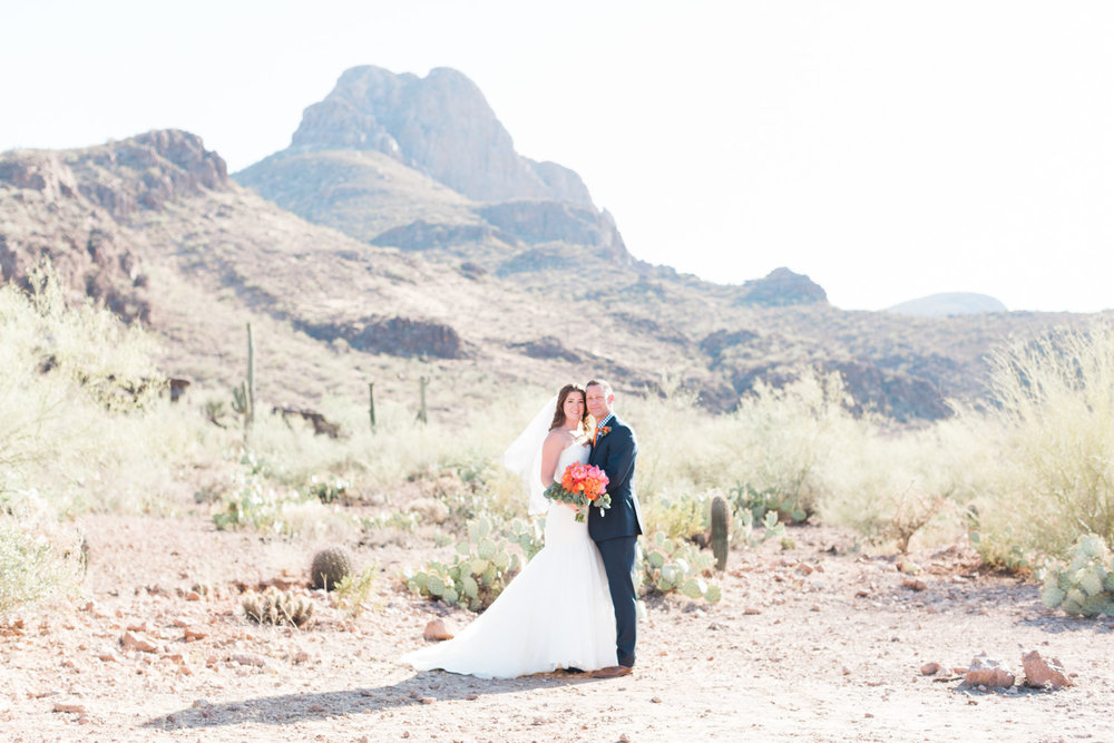Bride and groom standing in a gorgeous desert setting. Love those stunning mountain views an the cactus in the back