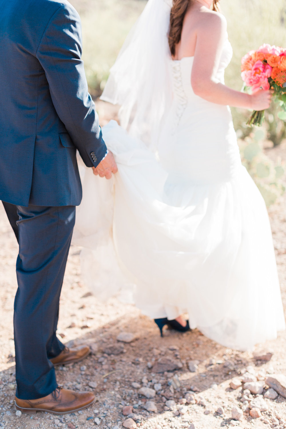 Groom carrying his brides dress as she treks through the rocky Tucson desert in heels.