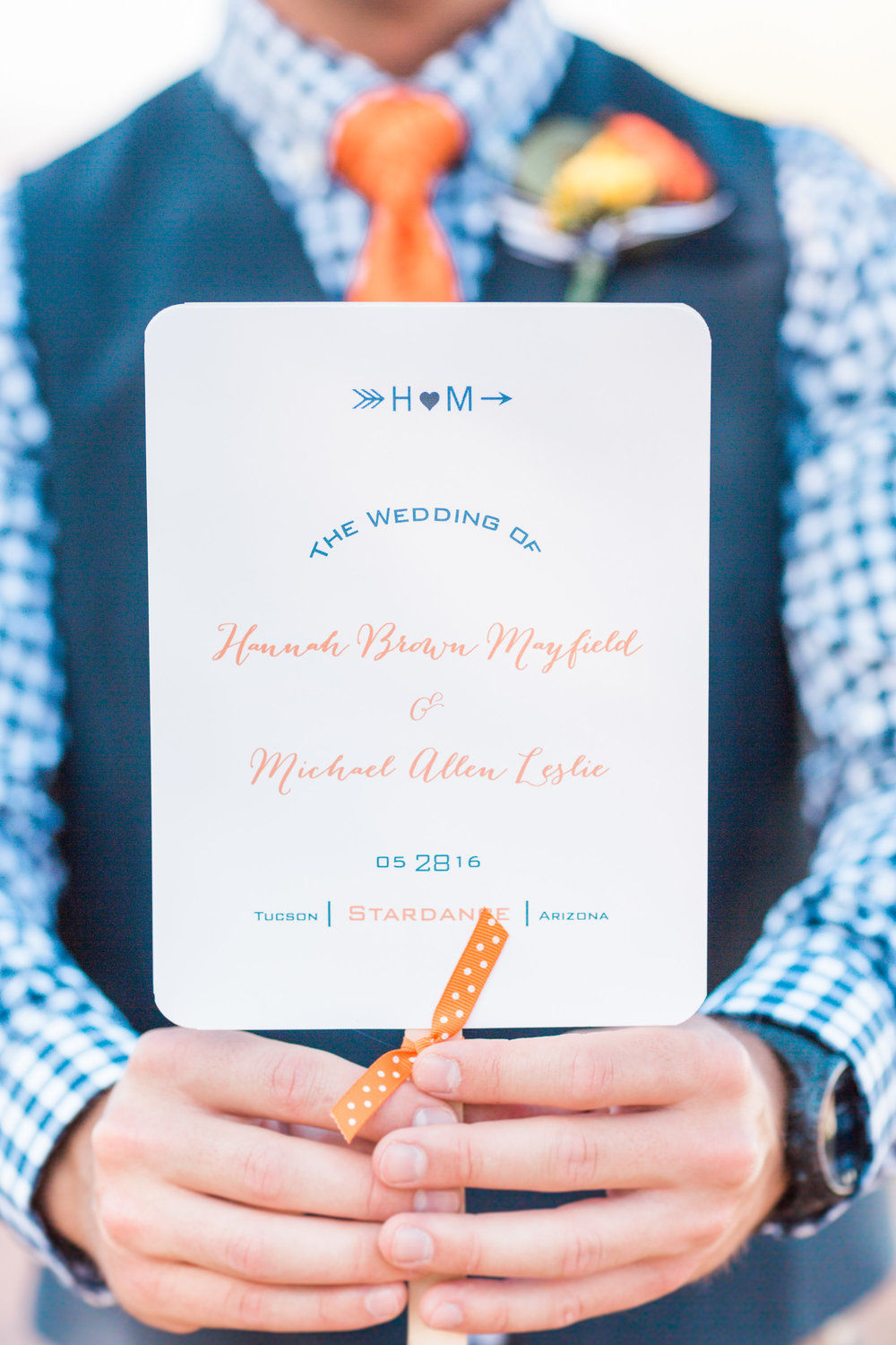 Groomsmen holding the wedding info that guests also used as fans. What a great idea for a hot wedding day!