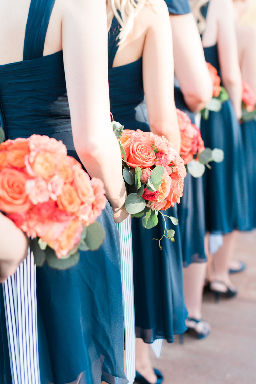 Bridesmaids holding bouquets during the ceremony.