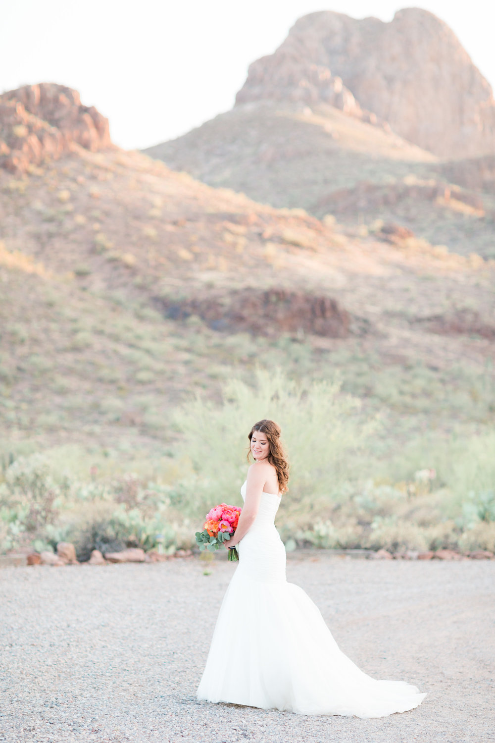 Gorgeous bride holding her bouquet in a gorgeous desert setting with huge mountains in the background. Love this wedding venue!