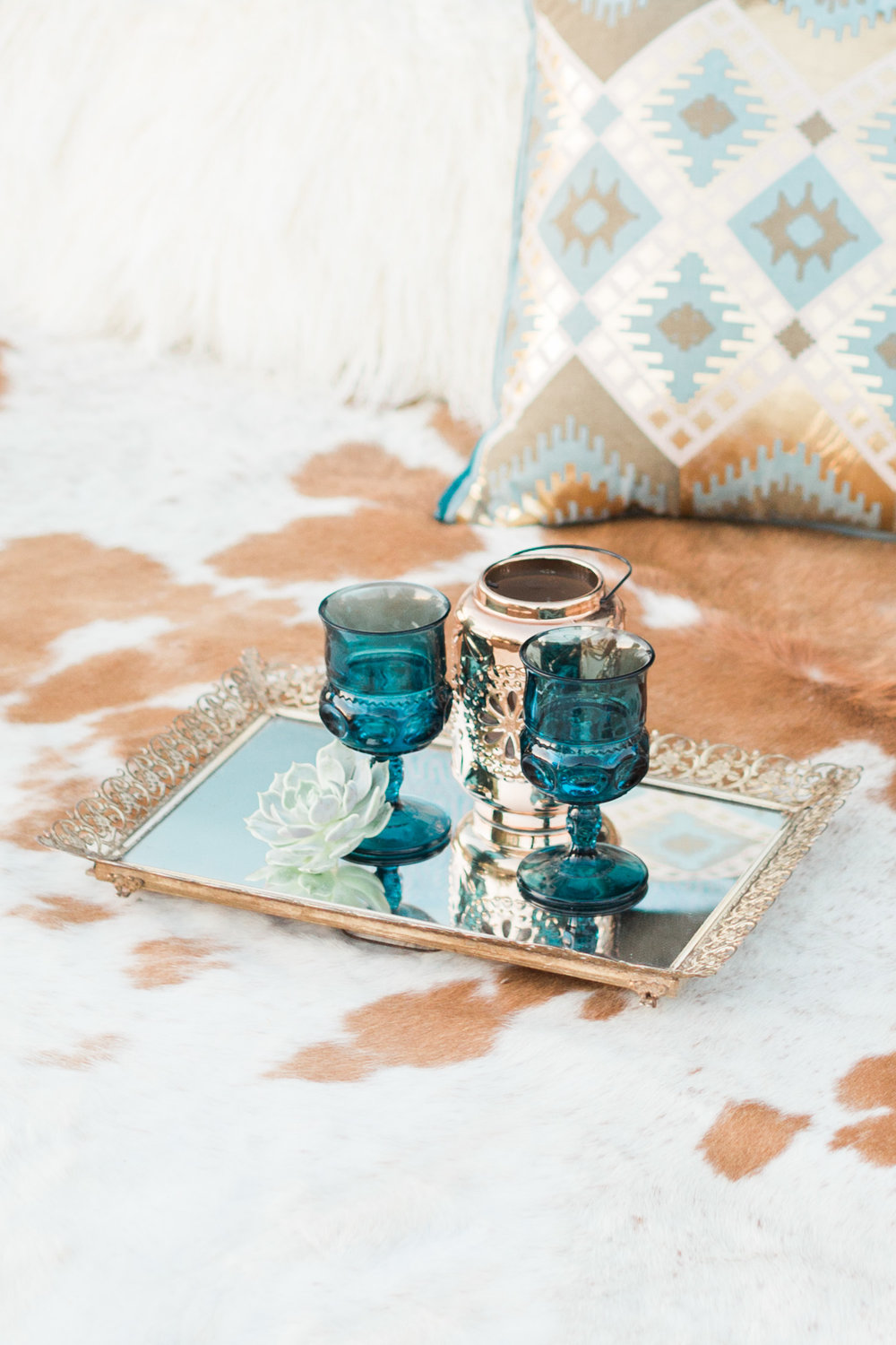 Blue antique goblets on a gold tray sitting on a cow hide rug