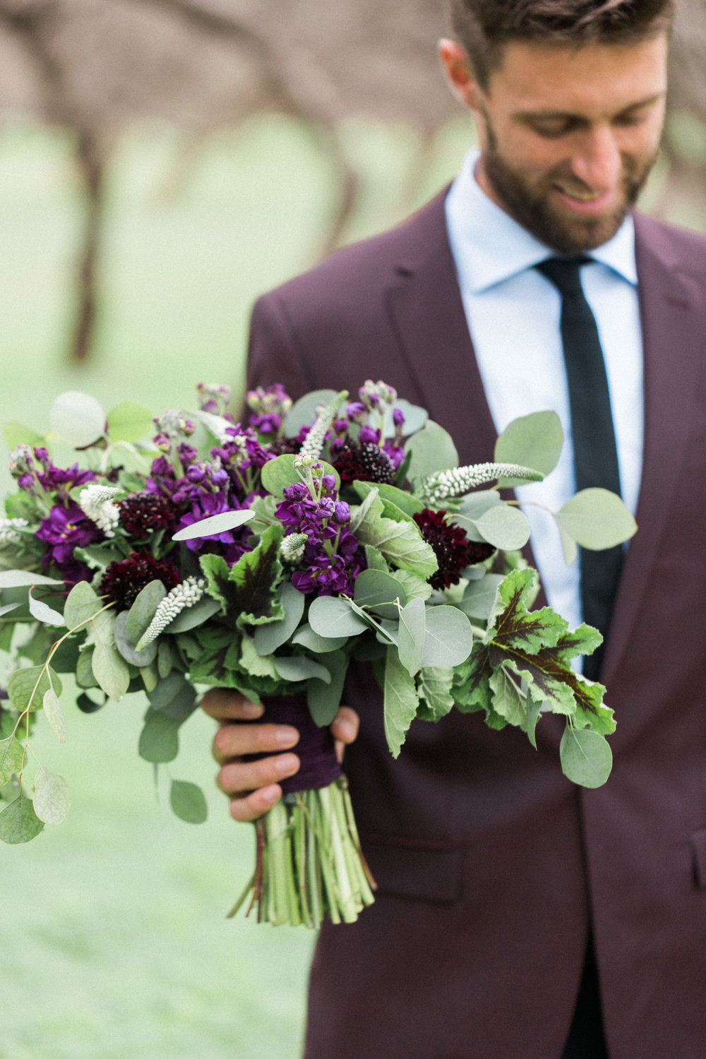 Groom smiling, holding bride's bouquet
