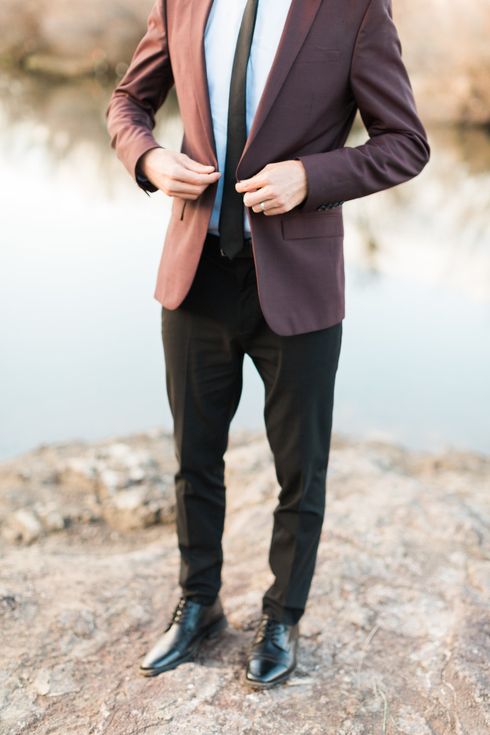 Groom buttoning his burgundy jacket on his wedding day.