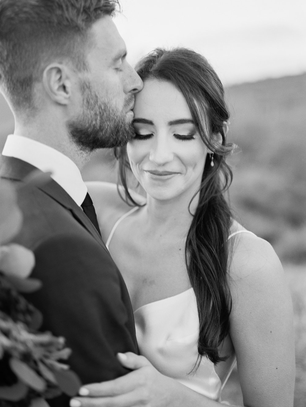 Kissing his bride's forehead. Romantic wedding day portrait in black and white.