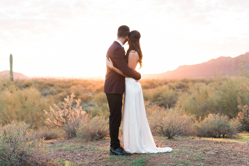 Peacefully looking our over the desert on their wedding day with a gorgeous Phoenix sunset in the background.