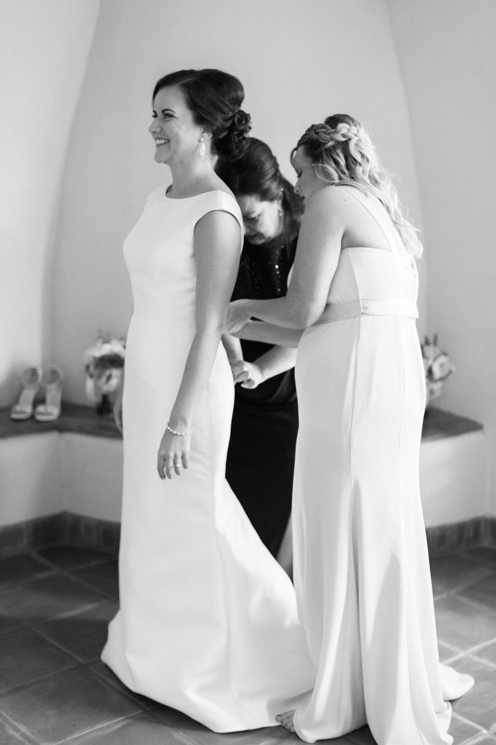Bride's mother & sister buttoning up her wedding dress at the gorgeous Tubac Golf Resort.
