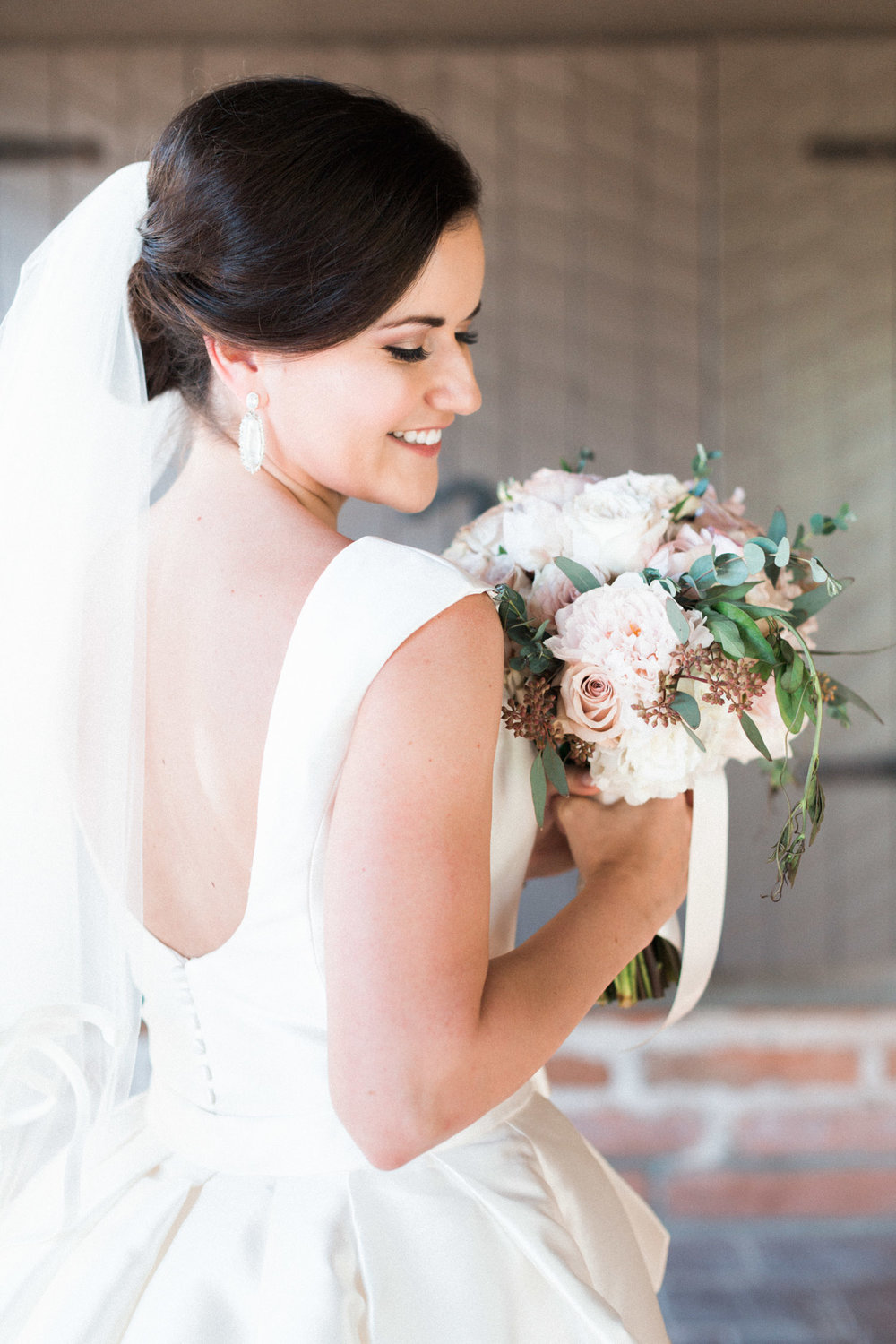 Bride posing with blush bouquet and stunning low back gown by Pronovias