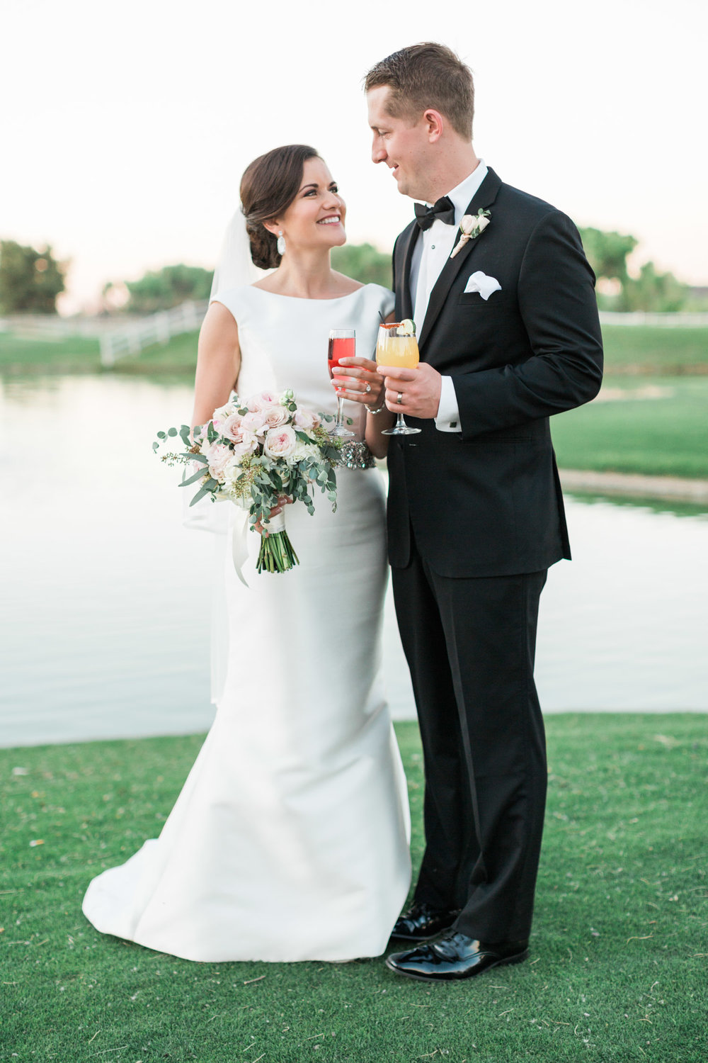 Couple cheersing with their signature wedding drinks in front of the lake at Tubac Golf Resort
