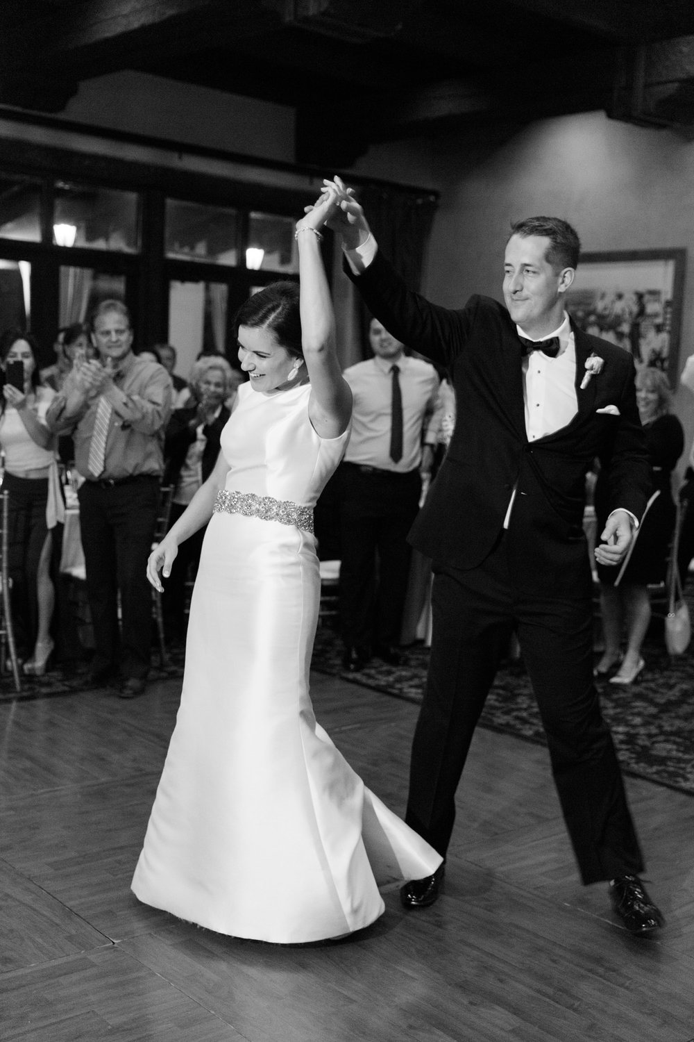 Groom spinning bride on the dancefloor during their first dance