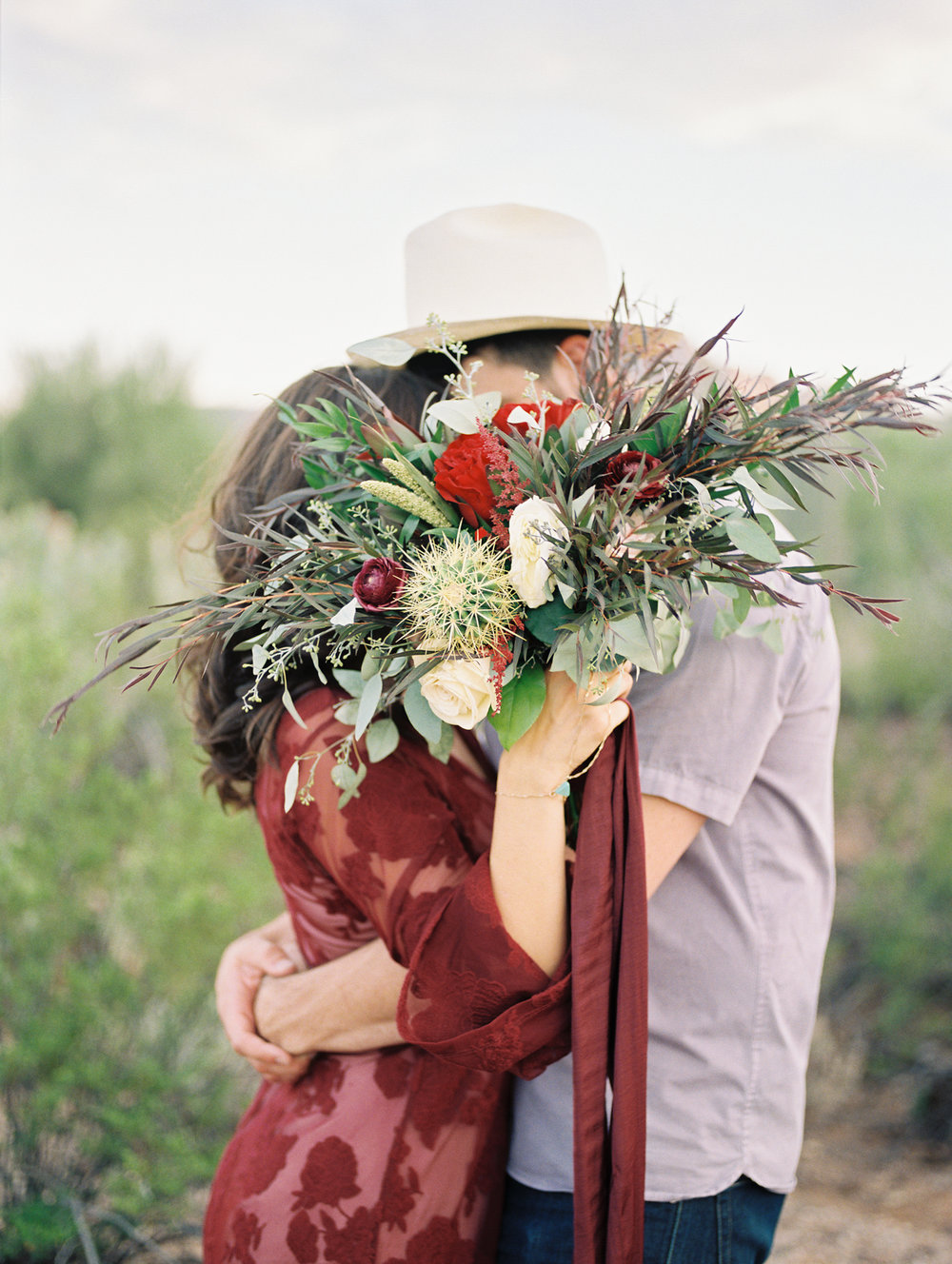 couple kissing, hiding behind beautiful fall bouquet. Such a cute shot by Tucson film wedding photographers Betsy & John