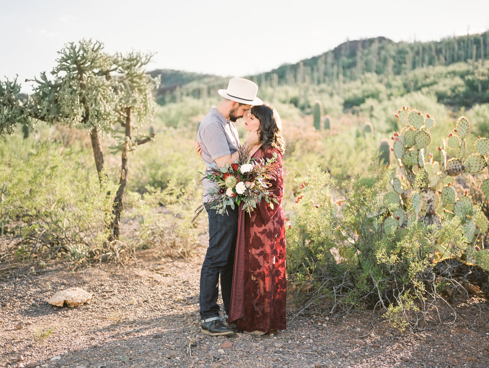 Couple standing in the desert about to kiss captured by Tucson Wedding Photographers, Betsy & John