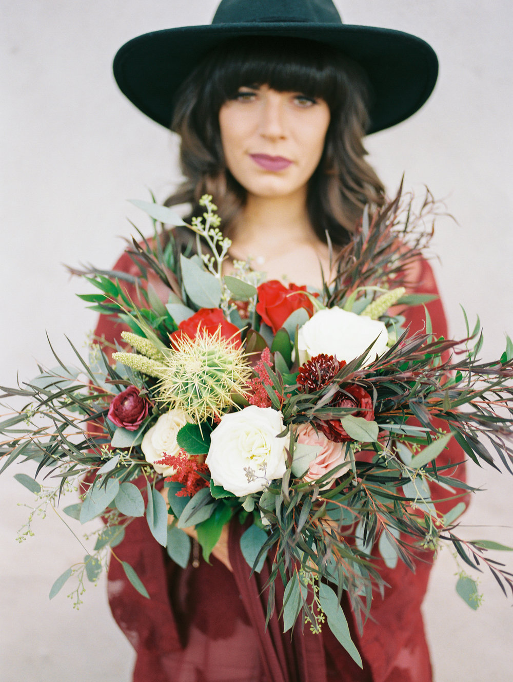 hipster bride wearing hat on her wedding day holding a desert bouquet