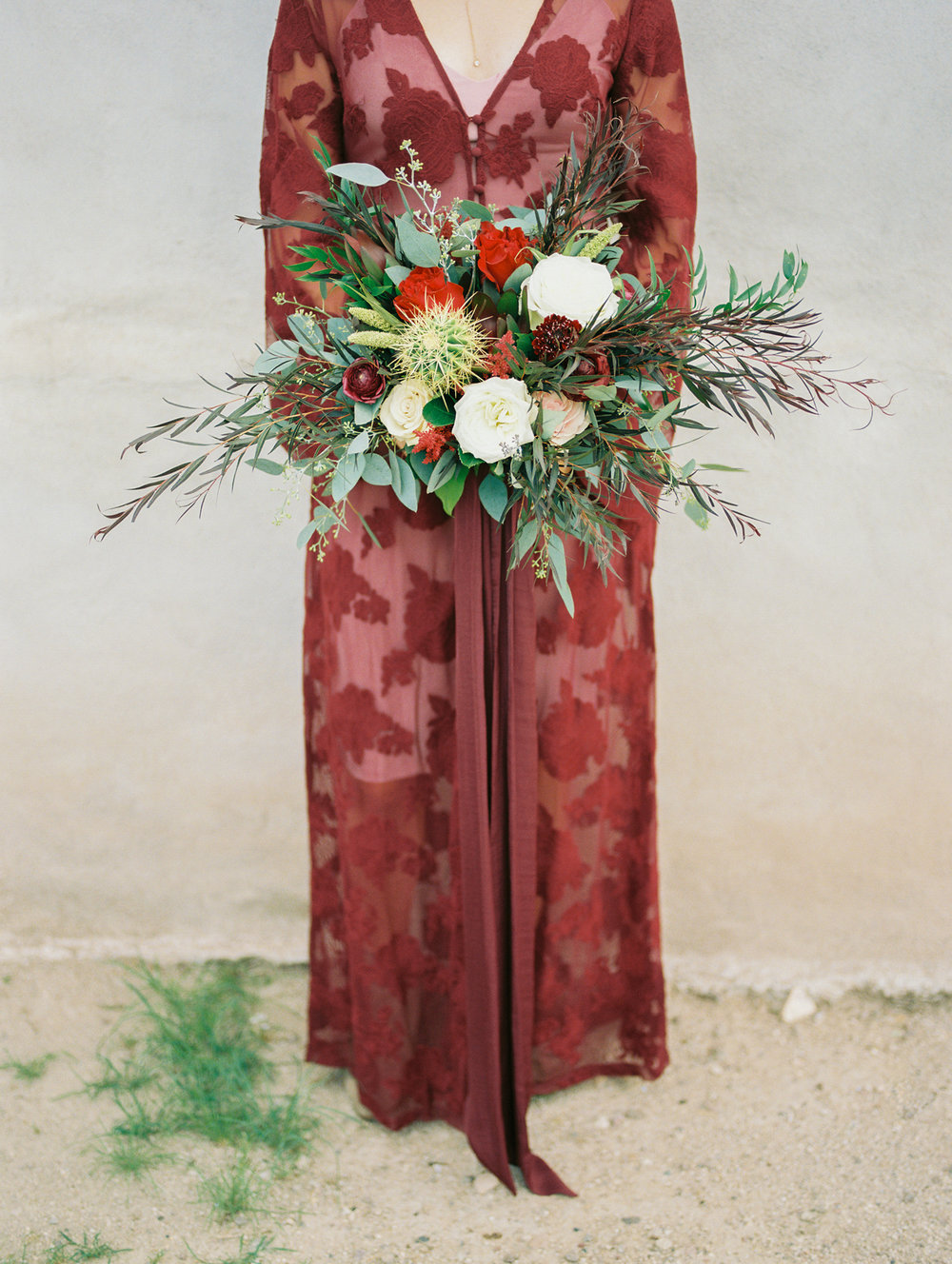 Bride in red burgundy lace dress holding desert fall bouquet with cactus