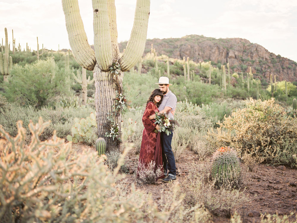 Couple in the Tucson desert with tons of saguaros in the background