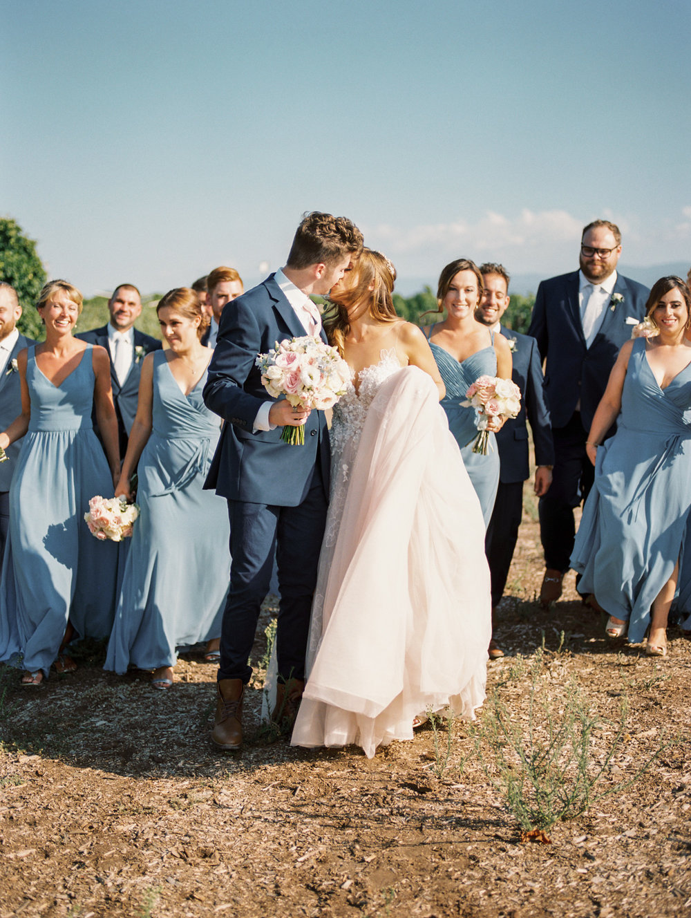 Bridal party walking through Wiens winery in Temecula | Harrison & Jocelyne's gorgeous Temecula wedding at Wiens Family Cellars captured by Betsy & John Photography