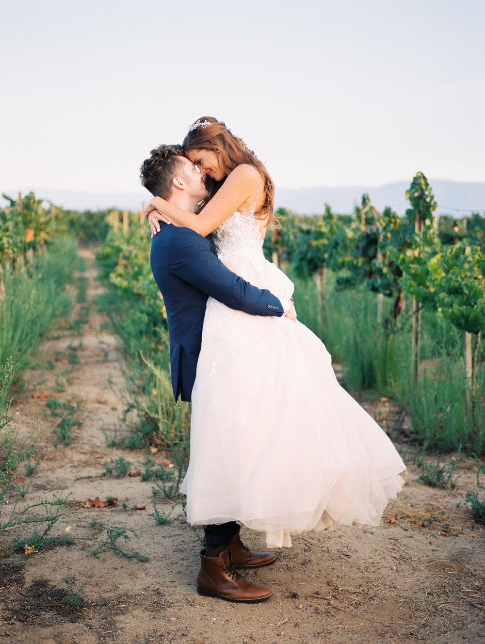 Groom smiling at bride  | Harrison & Jocelyne's gorgeous Temecula wedding day at Wiens Family Cellars captured by Temecula wedding photographers Betsy & John