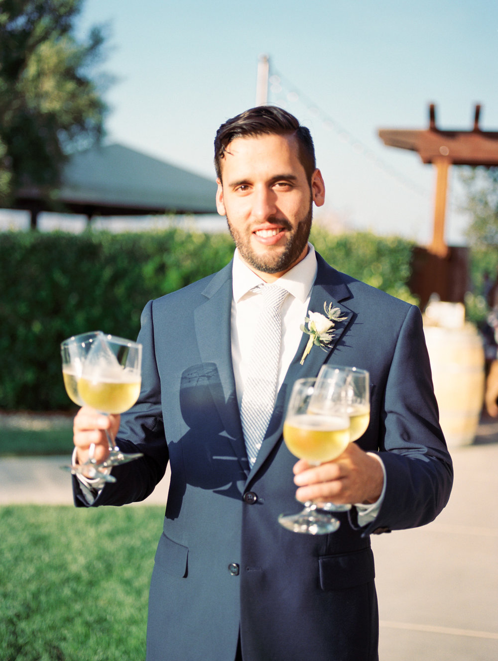 Groomsmen carrying 4 glasses of wine