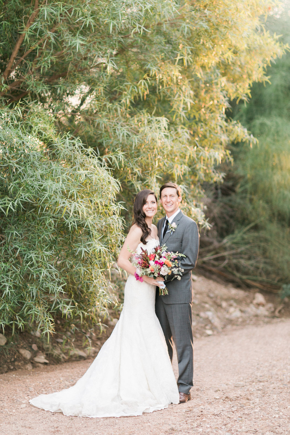 Bride and groom smiling at the camera with gorgeous golden light captured by Phoenix wedding photographers, Betsy & John