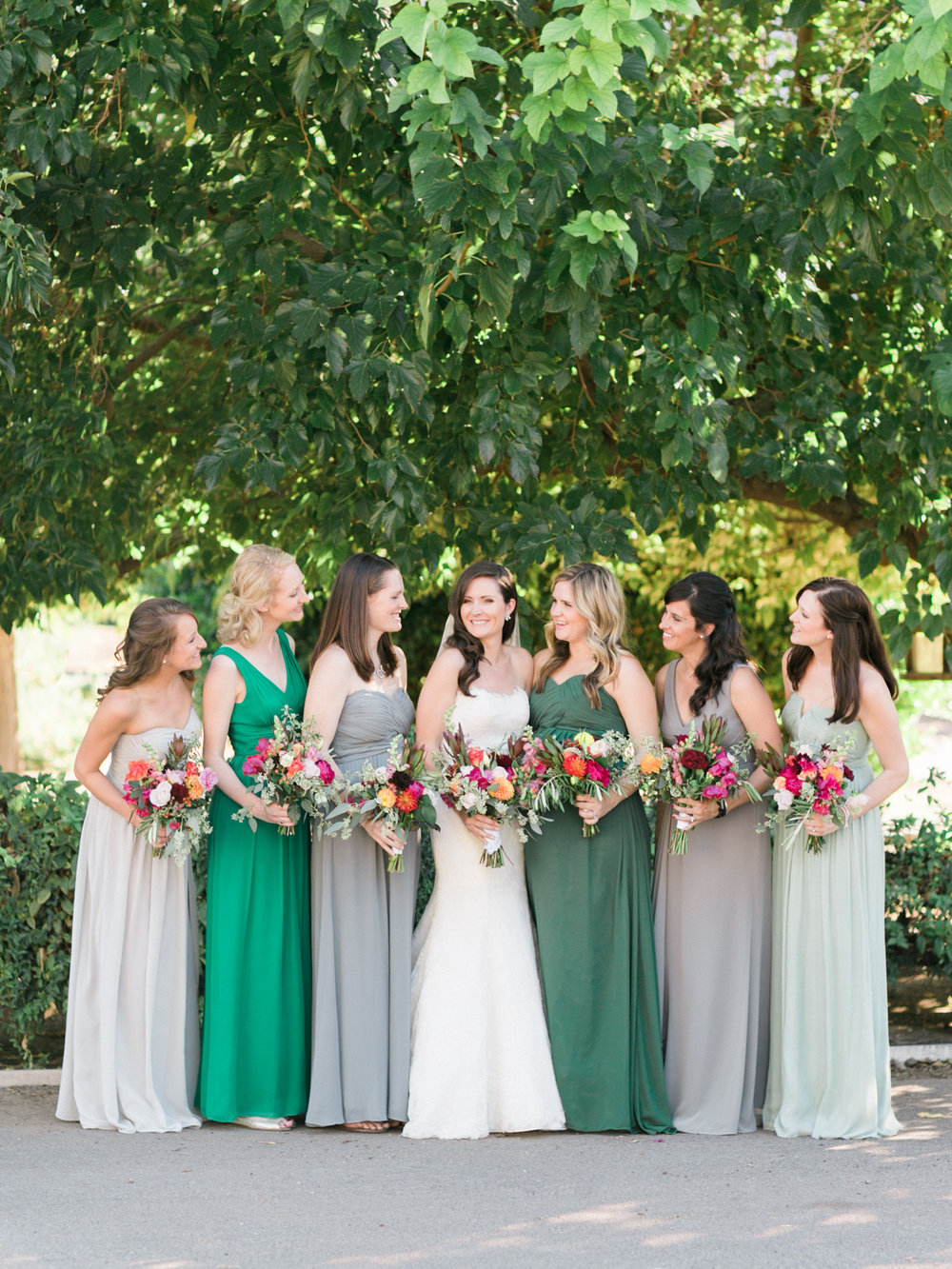 Gorgeous bridesmaids in greens, teals and grays smiling at the bride