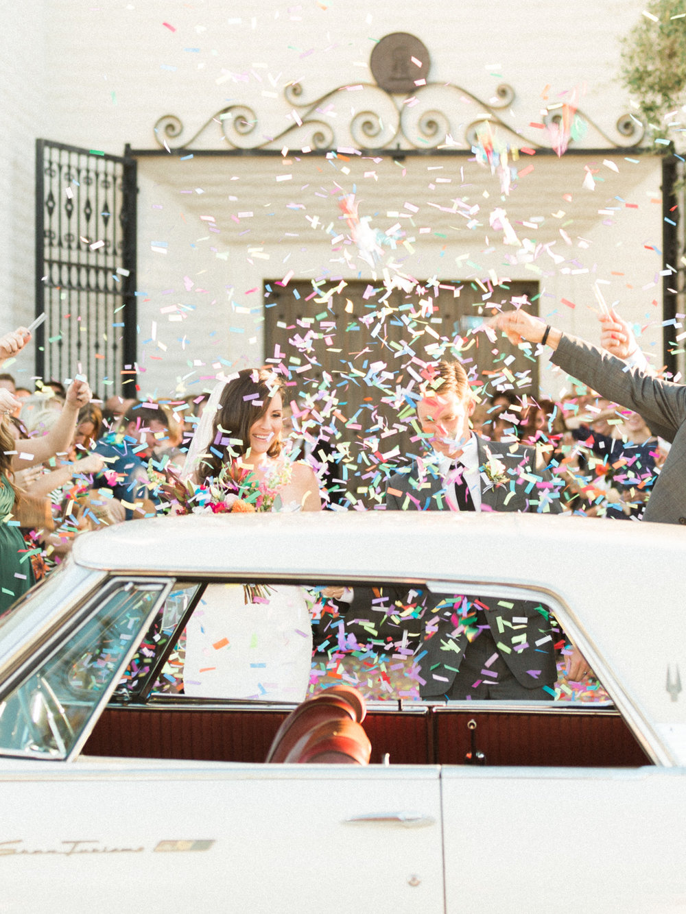 Confetti exit after ceremony, bride and groom getting into getaway car