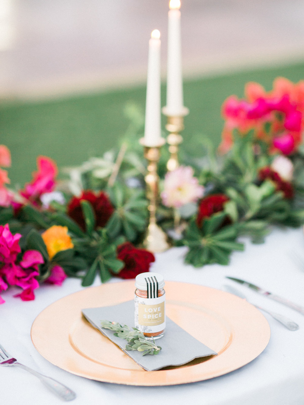 Gorgeous wedding table setting with brass candlesticks, greenery and bouganvillea