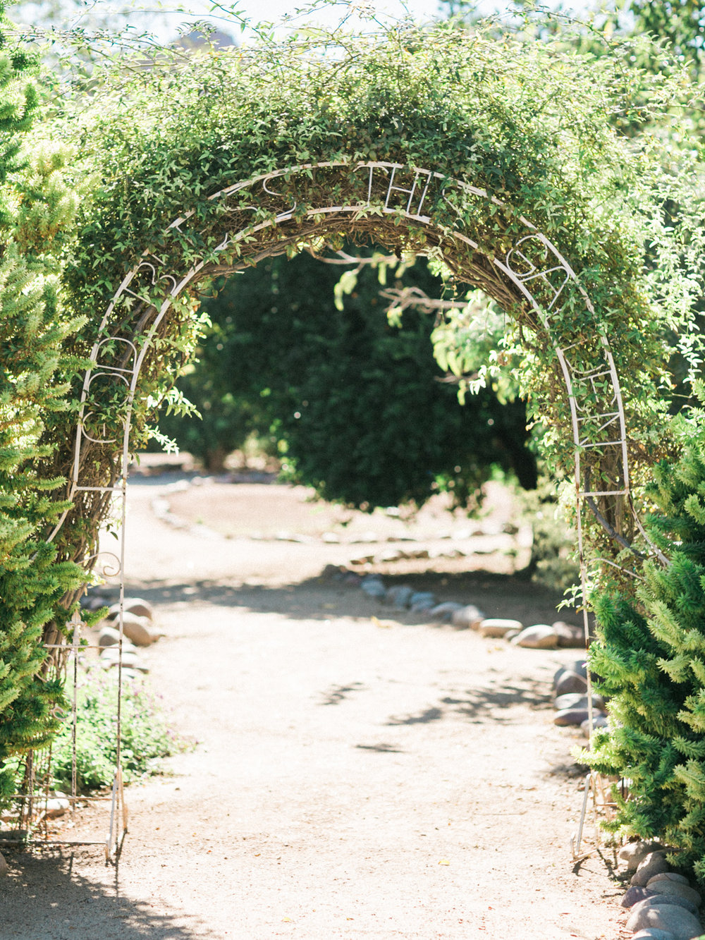 "Beautiful green archway that says ""God Bless this Garden"""