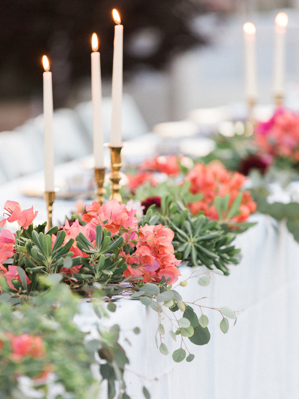 Beautiful head table settings with greenery, bougainvillea and brass candlestick holders