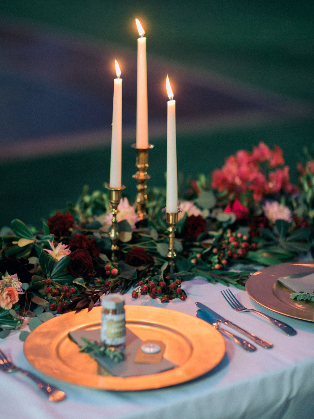 Table setting with gold chargers and beautiful brass candlesticks