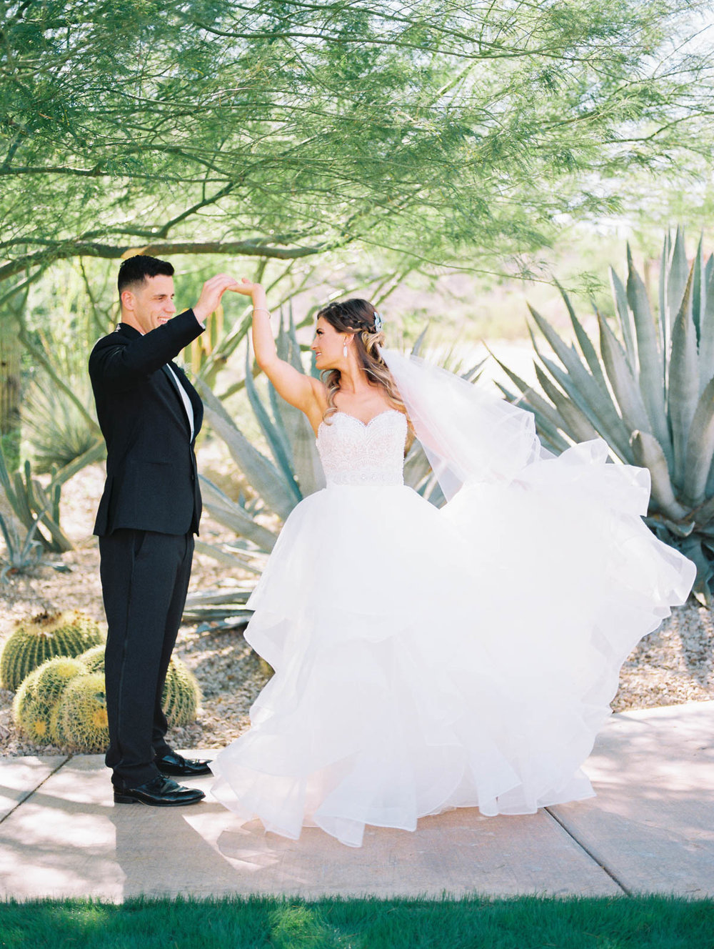 Groom twirling his beautiful bride captured by Tucson Wedding Photographers Betsy & John