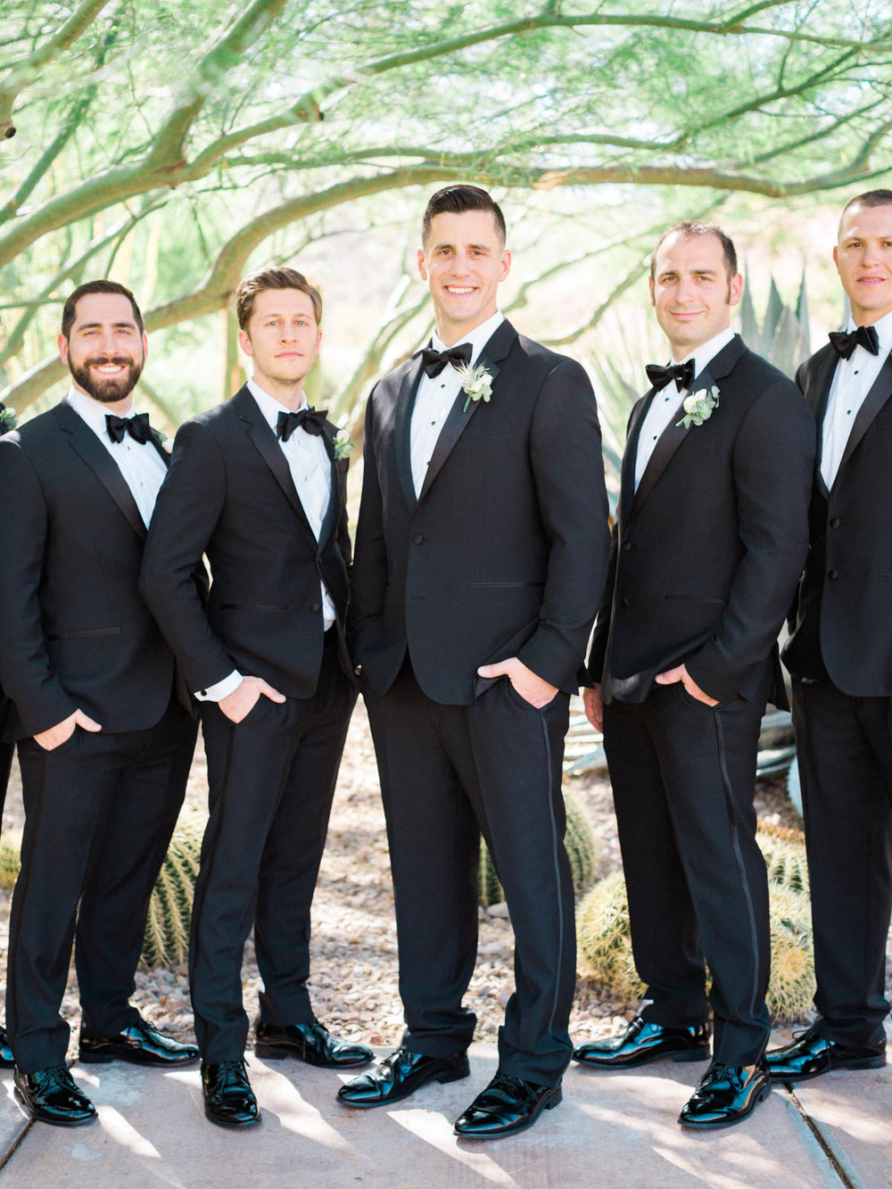 Groom and groomsmen in black tuxedos captured by Tucson Wedding Photographers Betsy & John