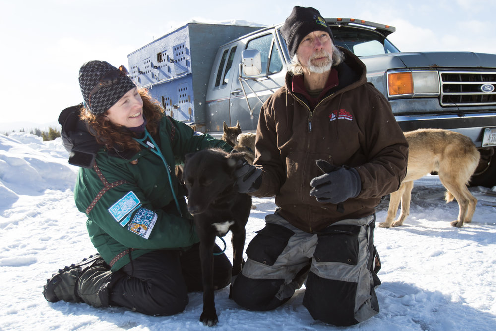 Vet technician Roberta Ronald (left) works with a dog with the assistance of musher Roy Etnire. Etnire competes in the 100-mile race.