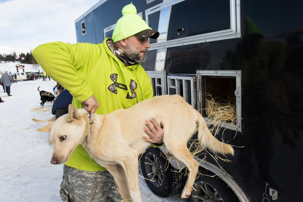 Handler James Pilcher unloads a dog from his team's truck.