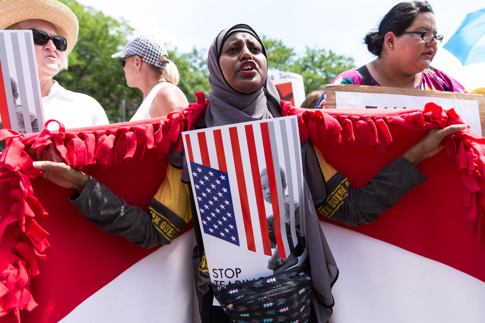 Zaynab Abdi, 22, a refugee from Yemen who's separated from her family due to U.S. immigration laws, holds up her country's flag during a march protesting federal immigration policies in Minneapolis, Minn. on June 30, 2018. (Lacey Young, MPR News)