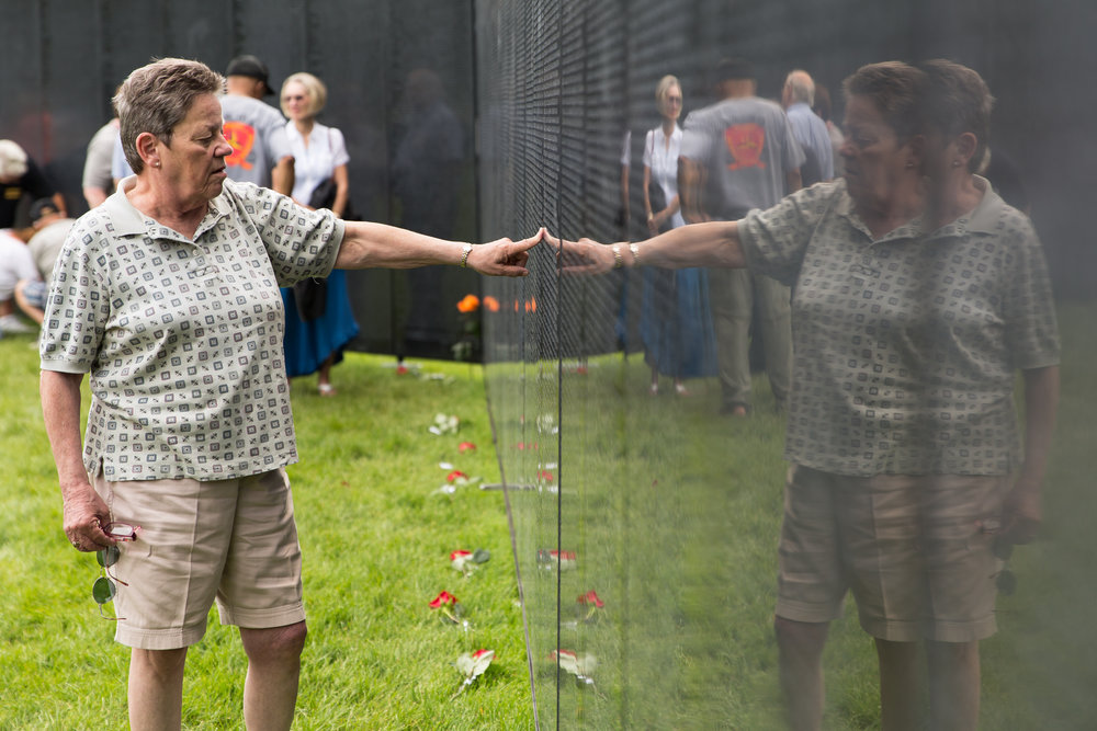 "Mary Clare Huberty touches her brother's name on ""The Wall that Heals,"" a three-quarter-scale model of the Vietnam Veterans Memorial, on the grounds of the state capitol in St. Paul, Minn. on June 21, 2018. (Lacey Young, MPR News)"