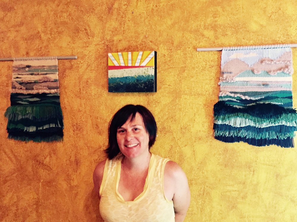 Ann Mackey with her weavings and paintings hung in Süp!