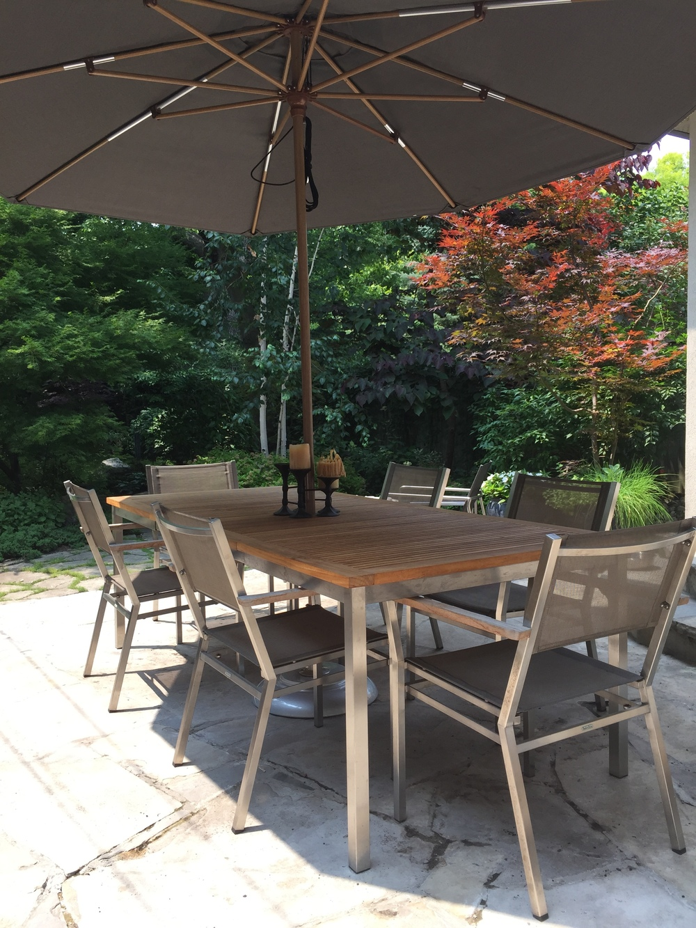Patio furniture from Gloster, Stainless and teak table. Dining chairs from Barlow Tyrie. Umbrella and base by Tuuci.